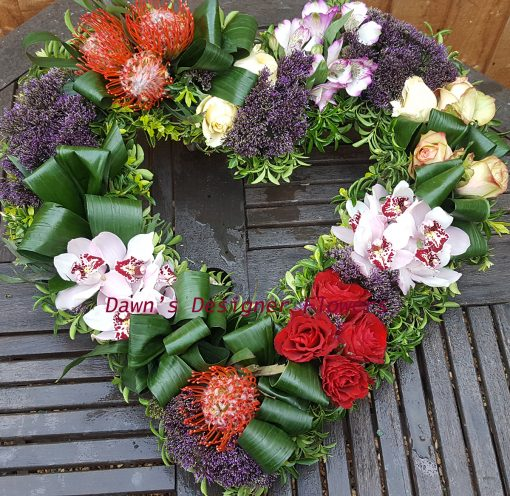 Heart tribute in lilac,orange and cream, from orchids,roses,trachelium